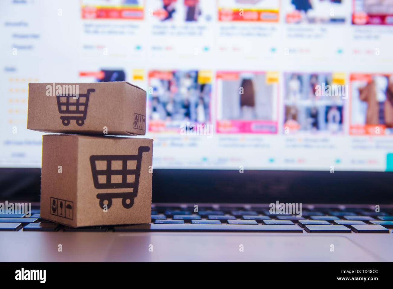 Online shopping - Paper cartons or parcel with a shopping cart logo on a laptop keyboard. Shopping service on The online web and offers home delivery. Stock Photo