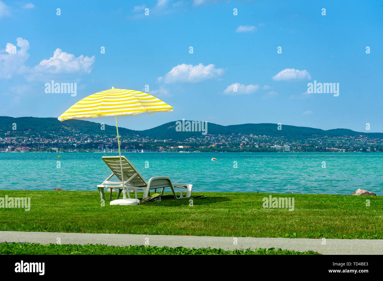 Stylish lounger plastic sunbed with yellow stripes sunshade beach umbrella on the green grass on beach at summer under open sky. Sunbed intended for - Stock Image