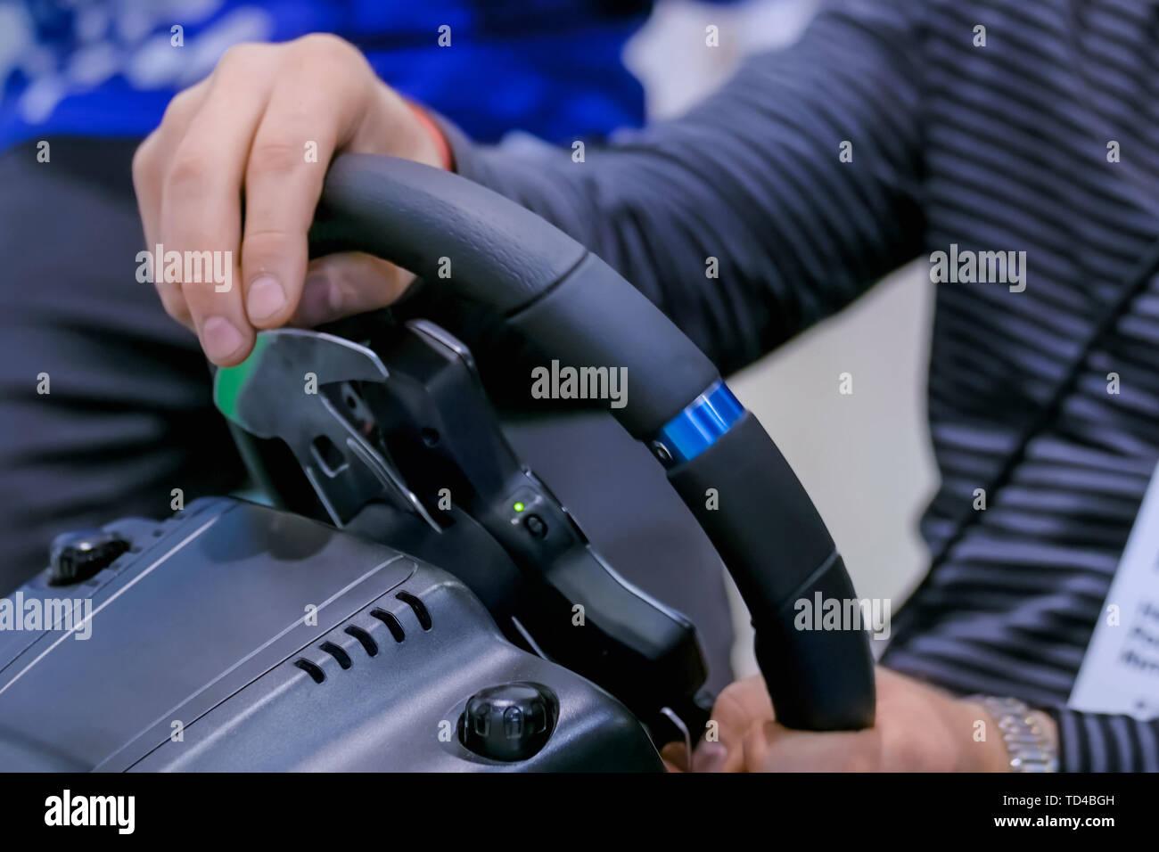 Man using gaming steering wheel joystick at technology exhibition - Stock Image