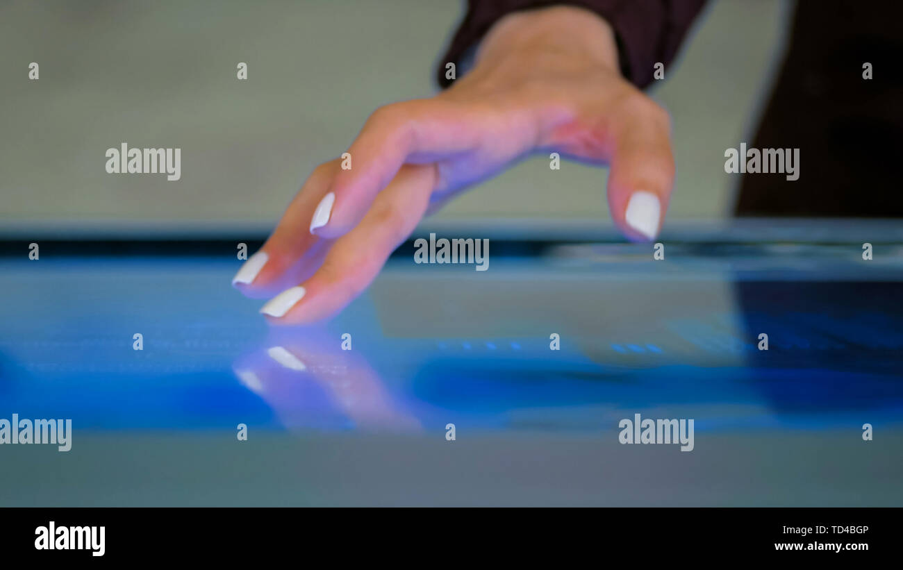 Woman using interactive touchscreen display at technology exhibition - Stock Image