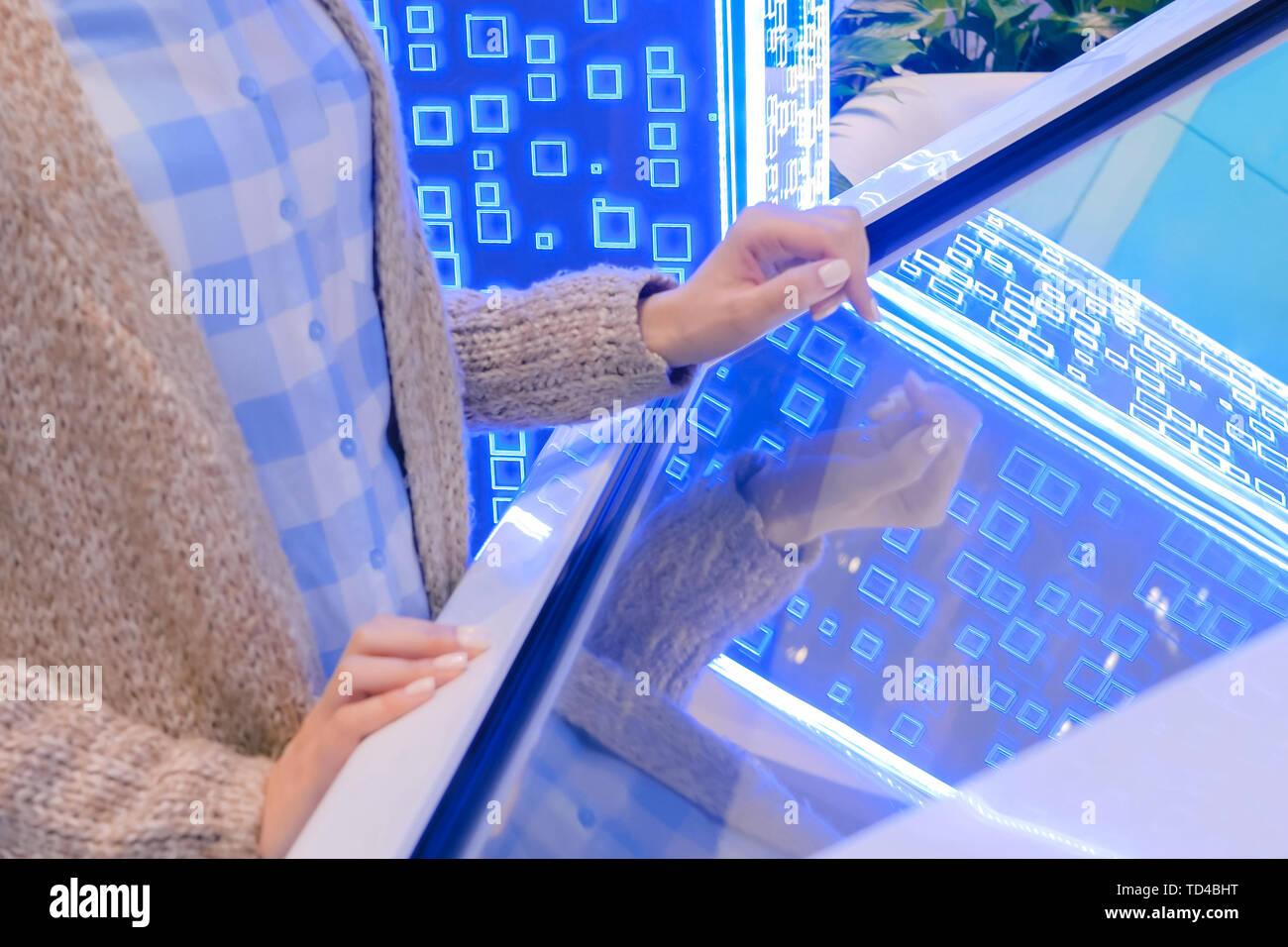 Woman using multimedia touchscreen display of interactive kiosk - Stock Image