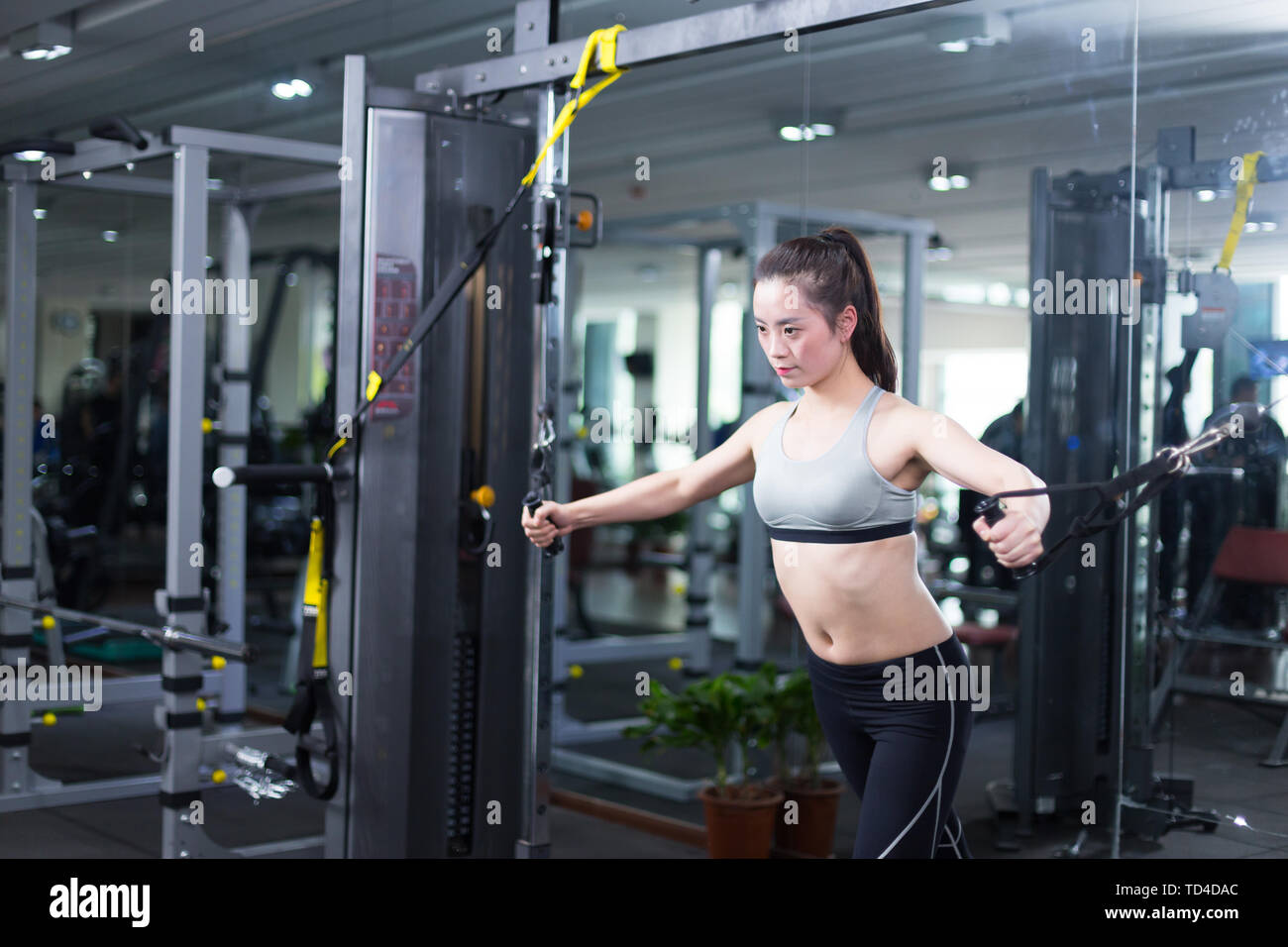 young asian girl working out in modern gym - Stock Image