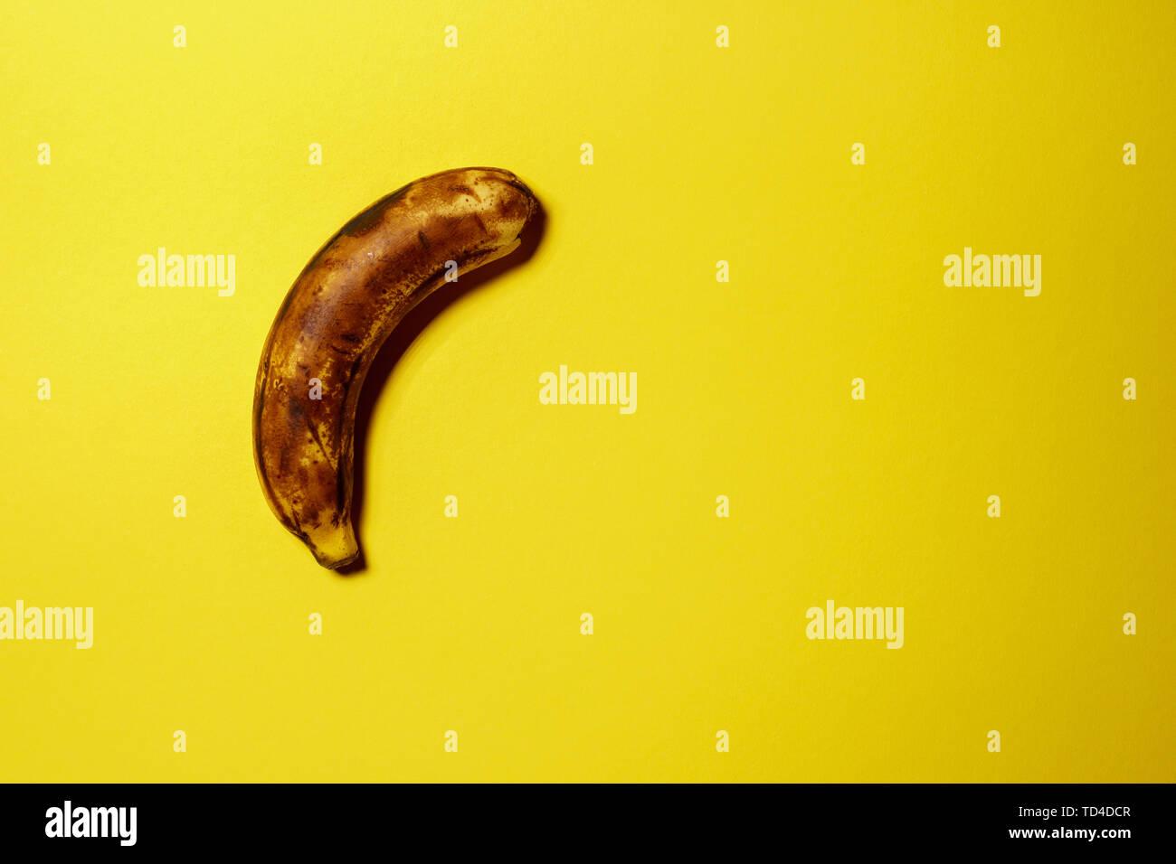 Single old rotten banana isolated on yellow background - Stock Image