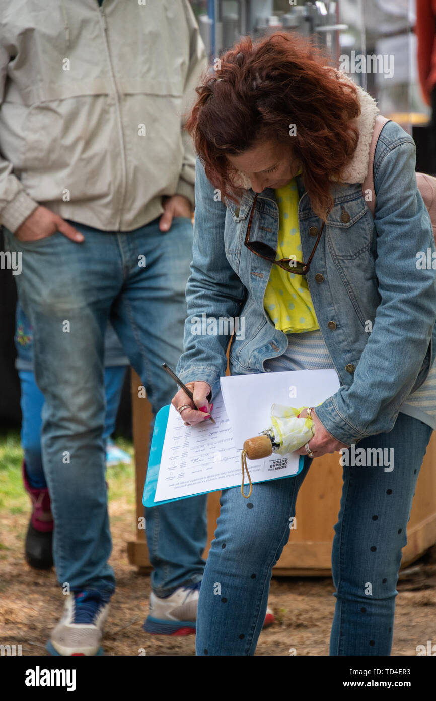 Princeton, New Jersey - April 28, 2019: Mature baby boomer woman is seen signing a petition for Moms Demand Action on gun control at a street fair on  - Stock Image