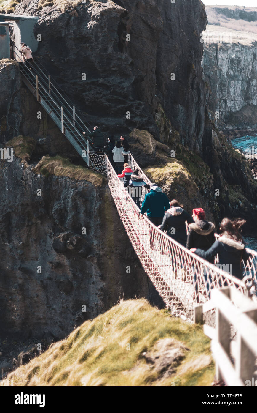 NORTHERN IRELAND, UK - 8TH APRIL 2019: Scared tourists cross the dangerous but beautiful Carrick-a-Rede Rope Bridge - Stock Image