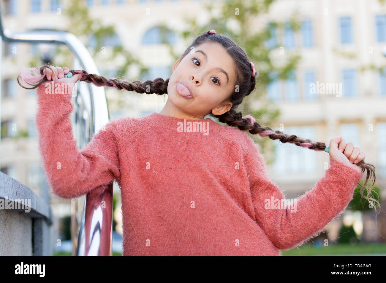 Having fun with her hair. Funny girl holding hair plaits on urban background. Small cute girl with long brunette hair showing tongue outdoor. Little hair model with crazy look. - Stock Image