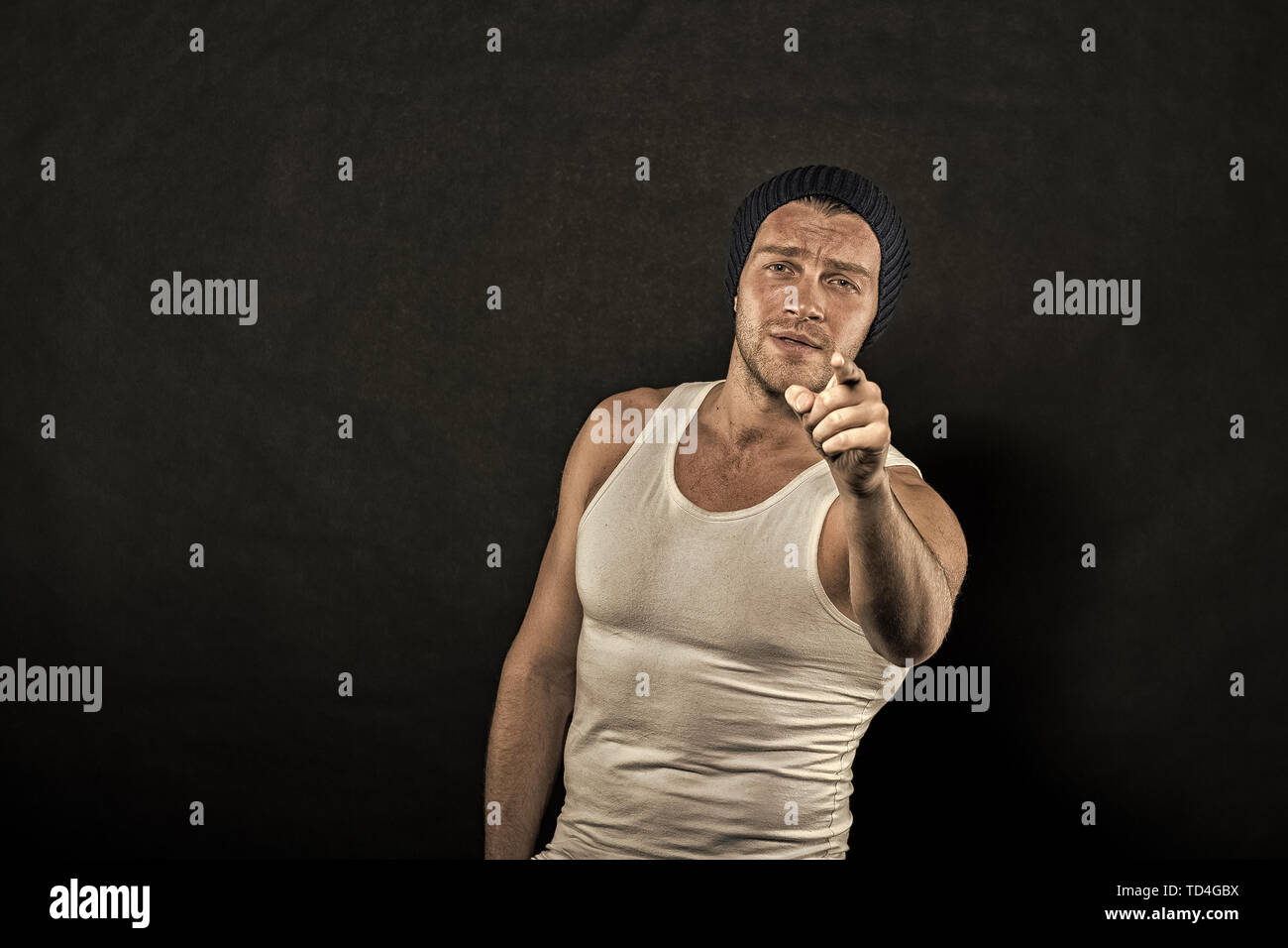 Man point finger on dark background. Macho in trendy vest and hat. Athlete with bristle on serious face. Sport and fitness. Fashion style and trend, vintage filter, copy space. - Stock Image