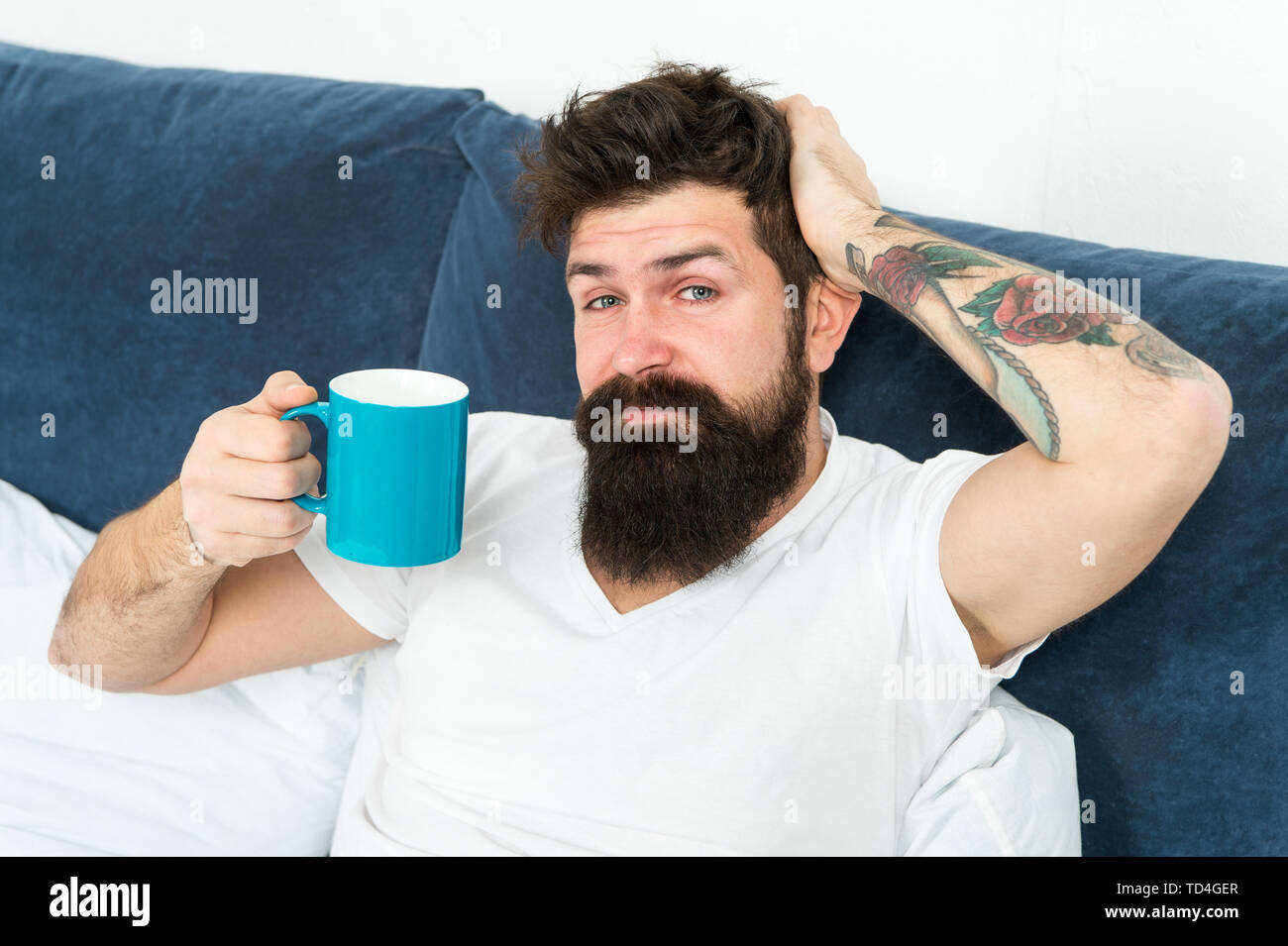 Tune in to new day. Morning awakening better with cup coffee. Relax and rest. Humanity runs on coffee. Man brutal handsome hipster relaxing bedroom drink coffee. Bearded guy enjoy morning coffee. - Stock Image