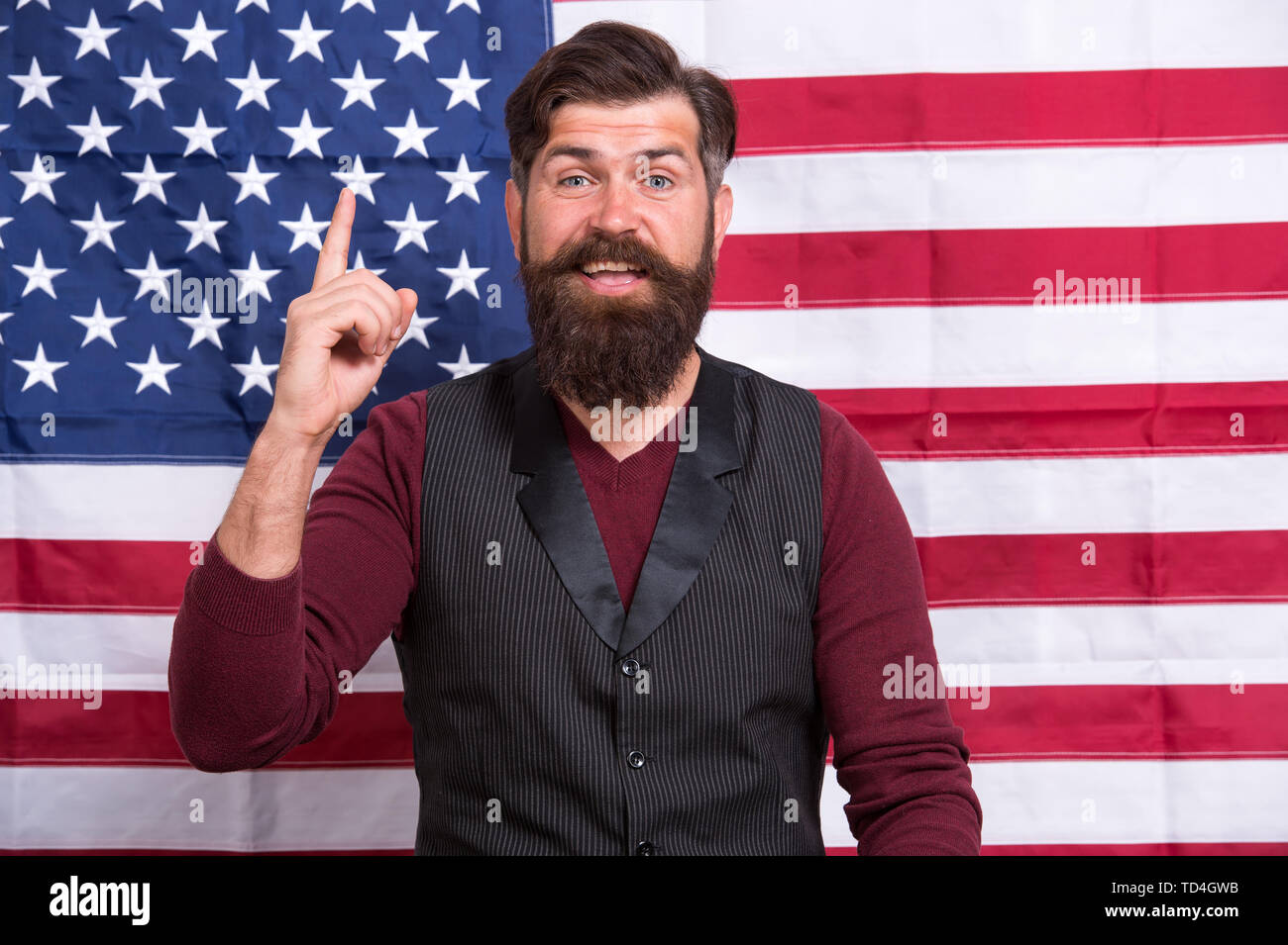 Idea and ideology. Patriotic concept. American lawyer teacher speaker or tv host american flag background. Love homeland. Man with beard and mustache with american flag. Make America great again. - Stock Image