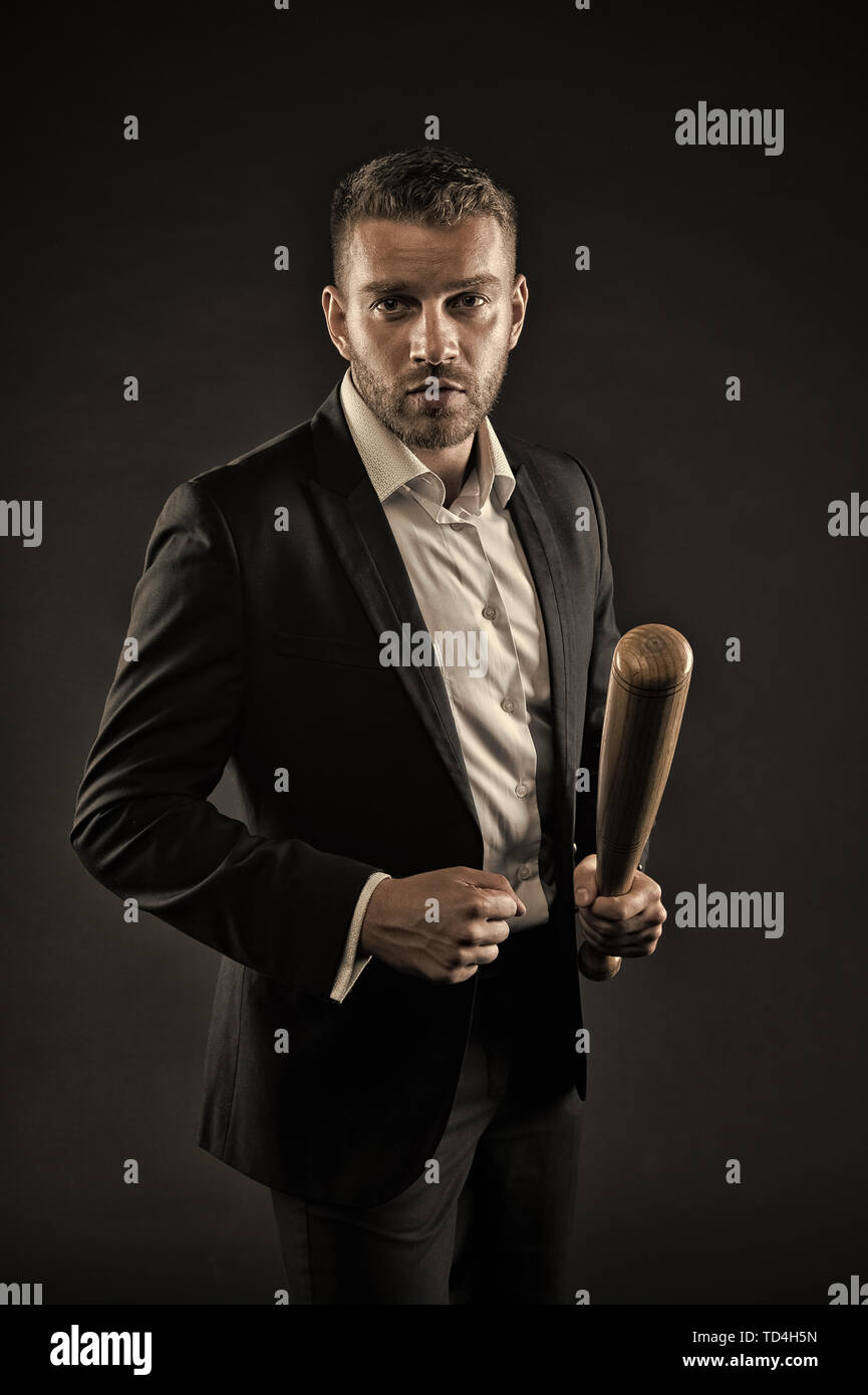 Businessman or man in formal suit on dark background. Man on strict face posing with wooden bat. Aggressive business concept. Man with bristle looks confident and threatening. - Stock Image