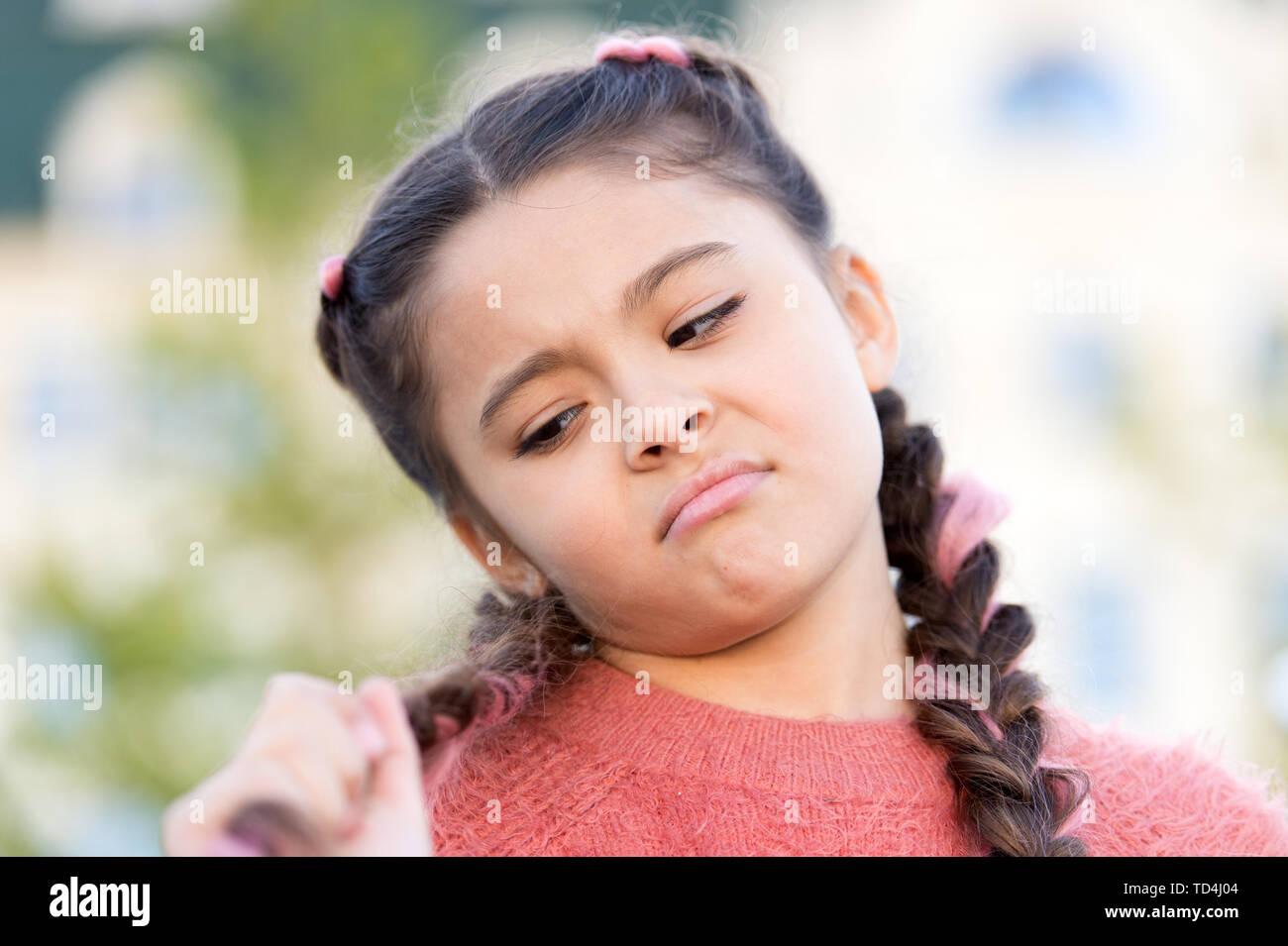 She needs a good hairdresser. Cute little girl looking at long braided hair. Kids hairdresser. Hairdresser salon for children. Doing her hair like hairdresser. - Stock Image