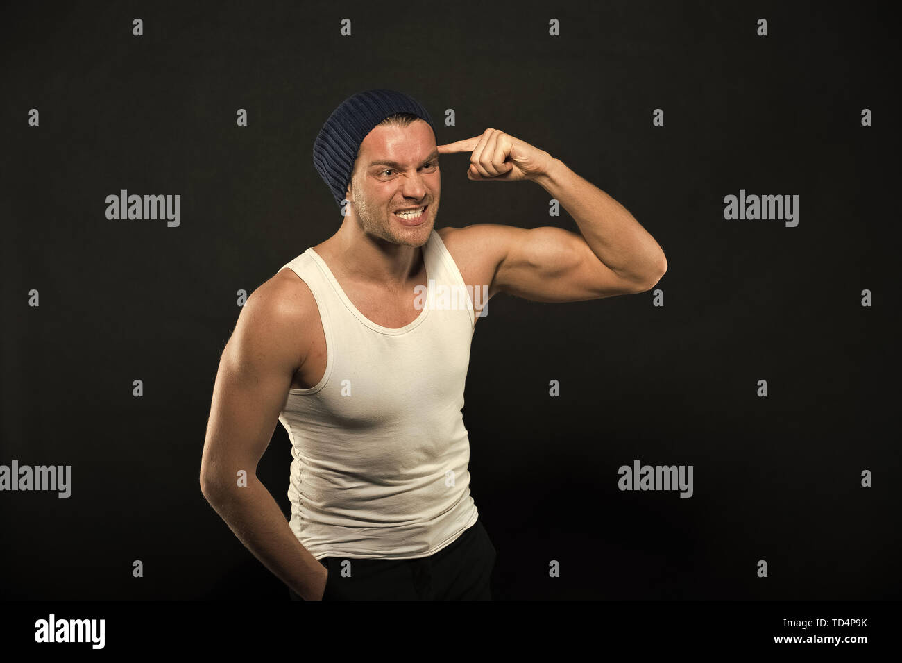 Man with finger at head. Macho with angry face. Athlete in fashion vest and hat with hand gesture. Anger and stress. Power in fitness and sport. - Stock Image
