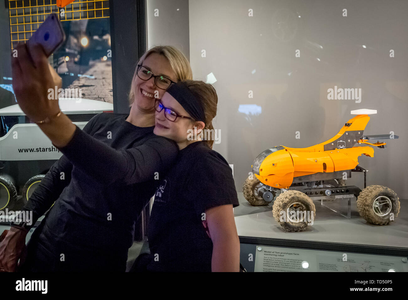"""London, UK. 12th June 2019. Driverless technology 'Who is in control?"""" exhibition is launched the Science Museum. Visitors take a selfie with 'Tom' a prototype farm monitoring robot designed by the Small Robot Company already in field trials on 20 farms across the UK. Exploring the history of self-driving vehicles, the exhibition also examines how much control we're willing to transfer to them and how their wider deployment could shape out habits, behaviour and society. Credit: Guy Corbishley/Alamy Live News Stock Photo"""