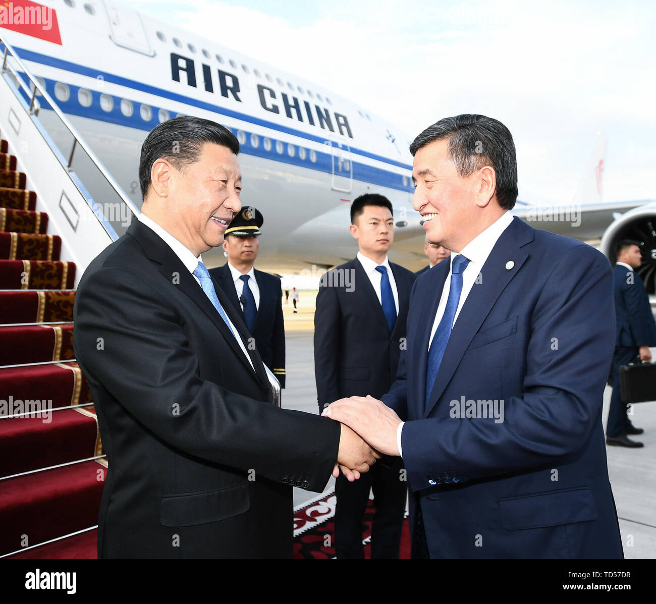 Bishkek, Kyrgyzstan. 12th June, 2019. Chinese President Xi Jinping is received by his Kyrgyz counterpart Sooronbay Jeenbekov upon his arrival in Bishkek, Kyrgyzstan, June 12, 2019. Xi arrived here Wednesday for a state visit to Kyrgyzstan and the 19th Shanghai Cooperation Organization (SCO) summit. Credit: Xie Huanchi/Xinhua/Alamy Live News - Stock Image