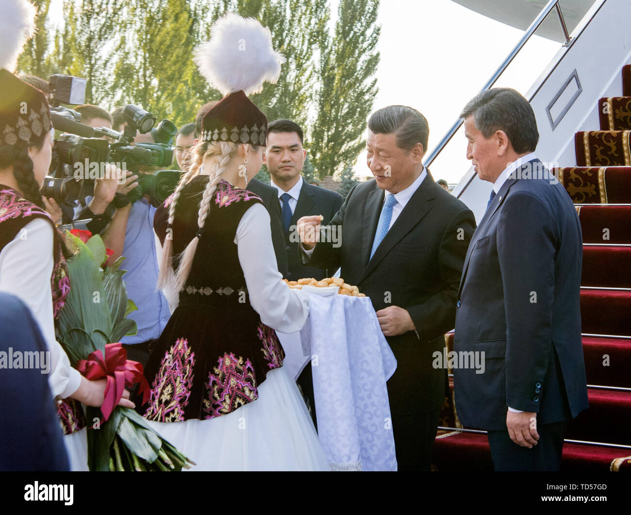 Bishkek, Kyrgyzstan. 12th June, 2019. Chinese President Xi Jinping arrives in Bishkek, Kyrgyzstan, June 12, 2019. Kyrgyz young people present flowers, bread and honey to Xi as a way to welcome distinguished guest. Xi arrived here Wednesday for a state visit to Kyrgyzstan and the 19th Shanghai Cooperation Organization (SCO) summit. Credit: Li Xueren/Xinhua/Alamy Live News - Stock Image