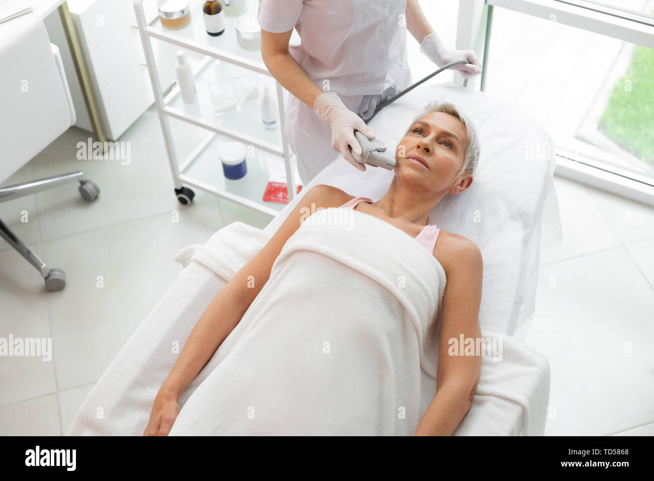 Latest methodology. Serious mature woman receiving a dermadrop TDA procedure while visiting a cosmetologist - Stock Image