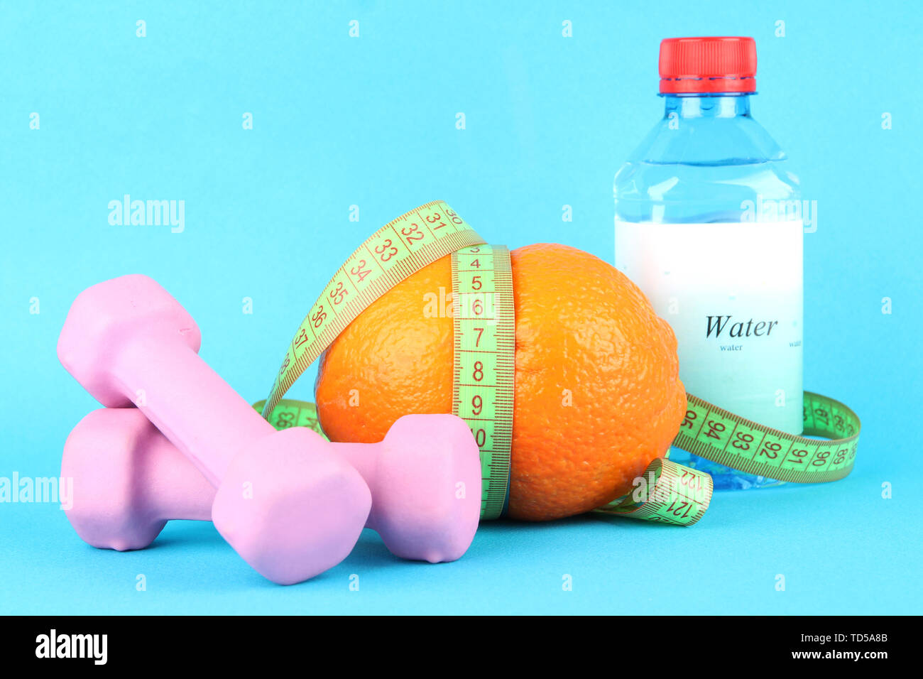 Orange with measuring tape, dumbbells and bottle of water, on color background - Stock Image