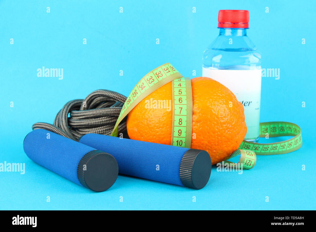 Orange with measuring tape,skipping rope and bottle of water, on color background - Stock Image