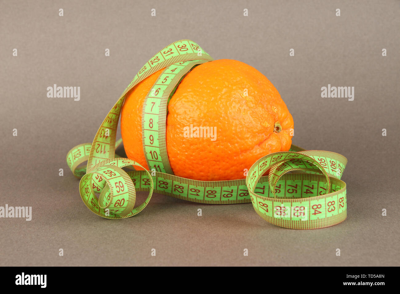 Orange with measuring tape, on color background - Stock Image