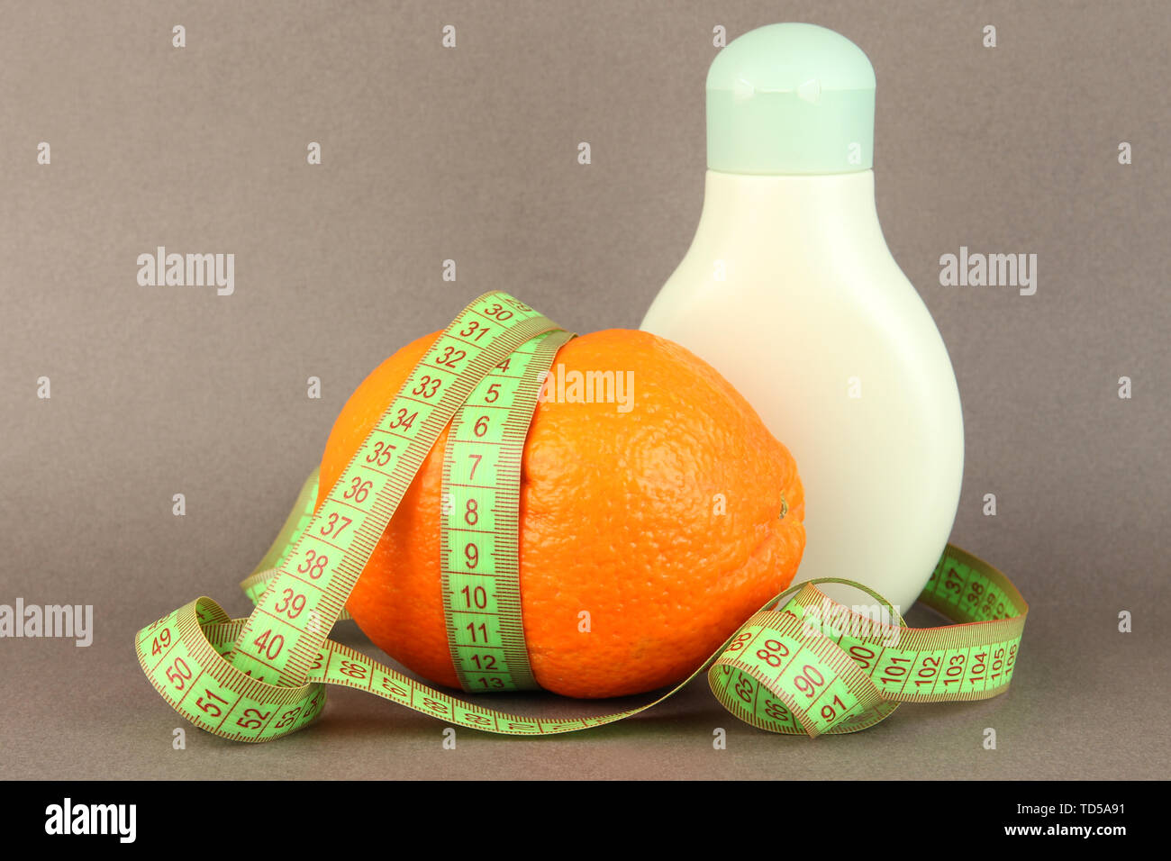 Orange with measuring tape and body cream, on color background - Stock Image