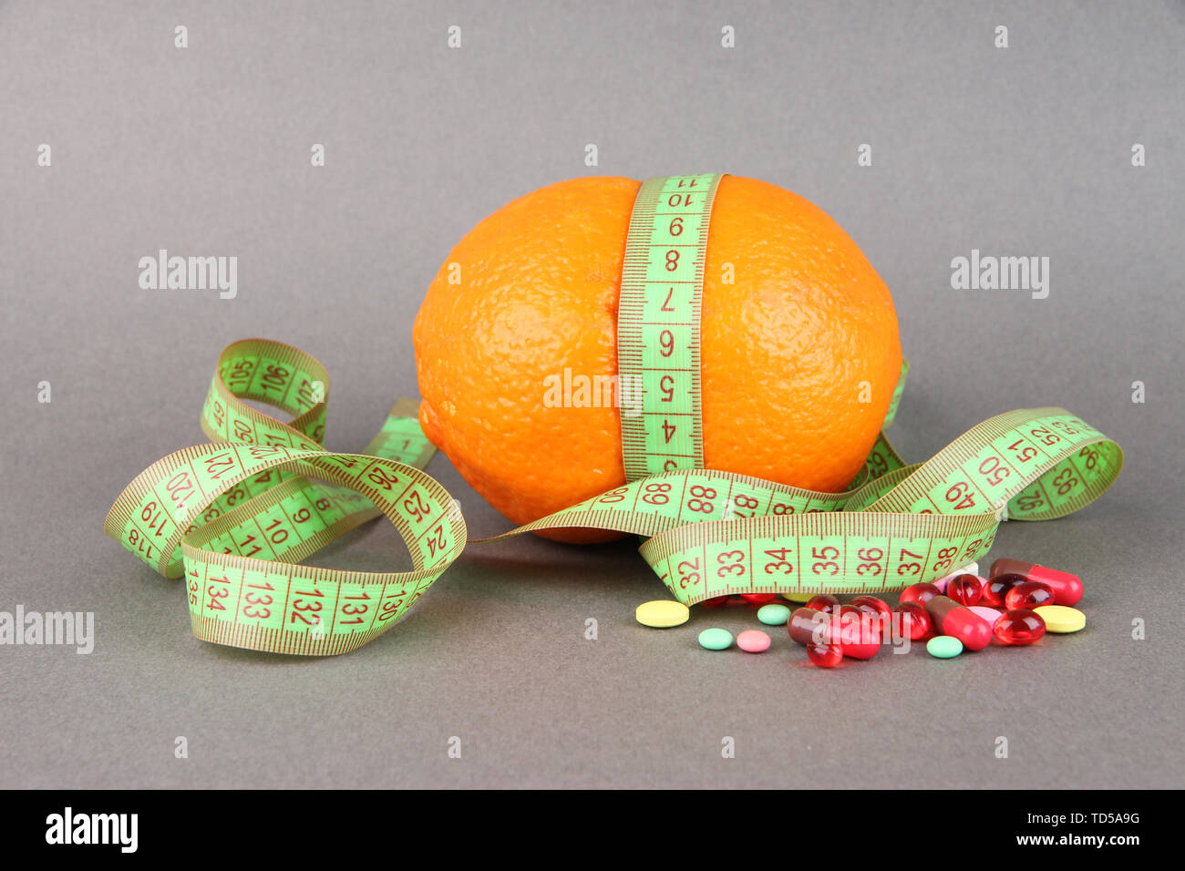 Orange with measuring tape and multicolor pills, on color background - Stock Image
