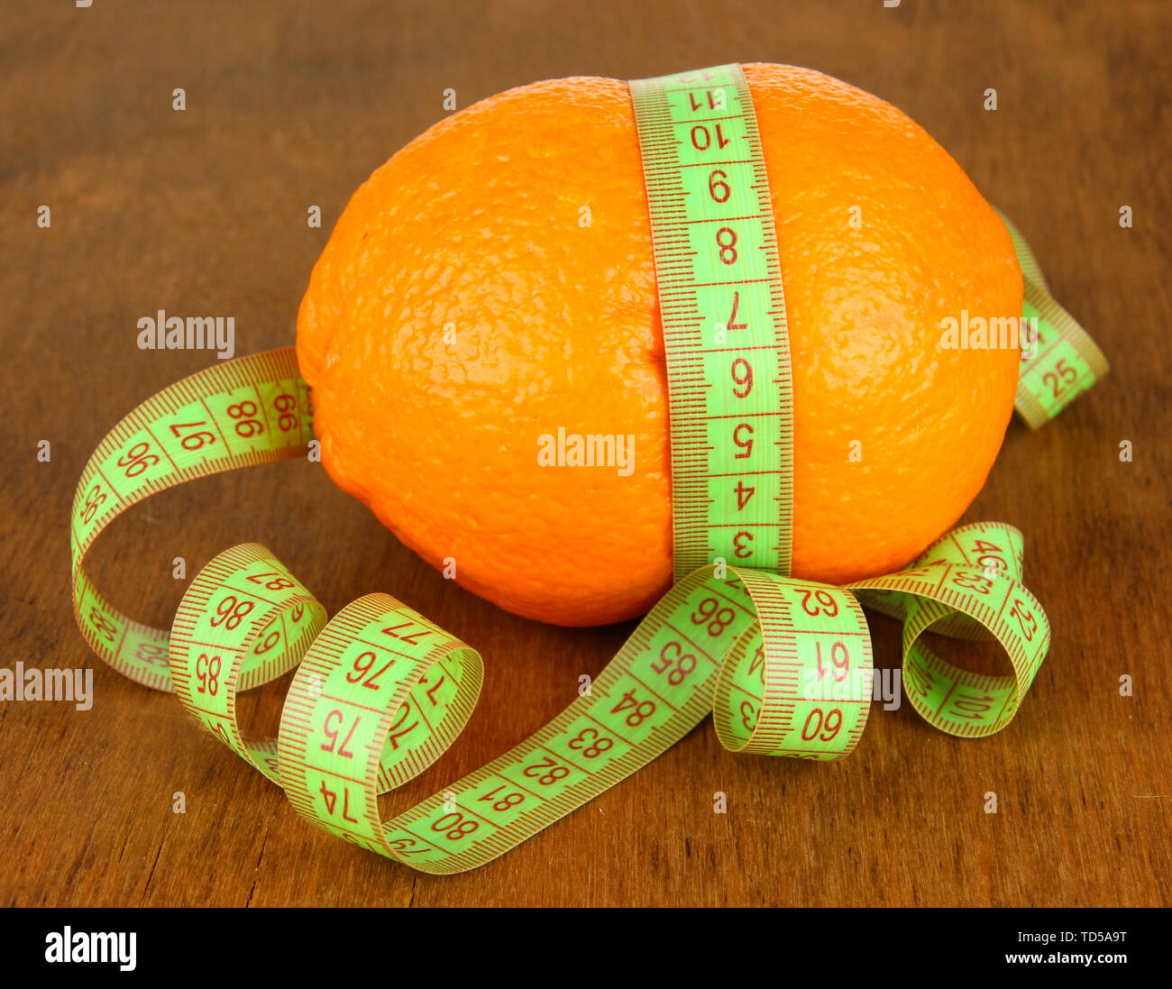 Orange with measuring tape, on wooden background - Stock Image