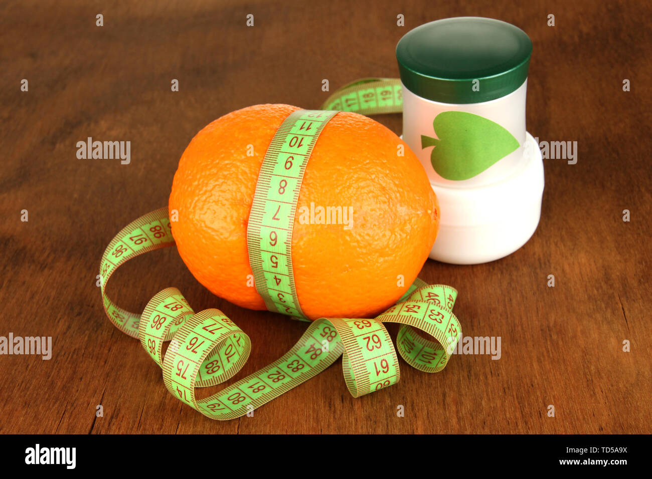 Orange with measuring tape and body cream, on wooden background - Stock Image