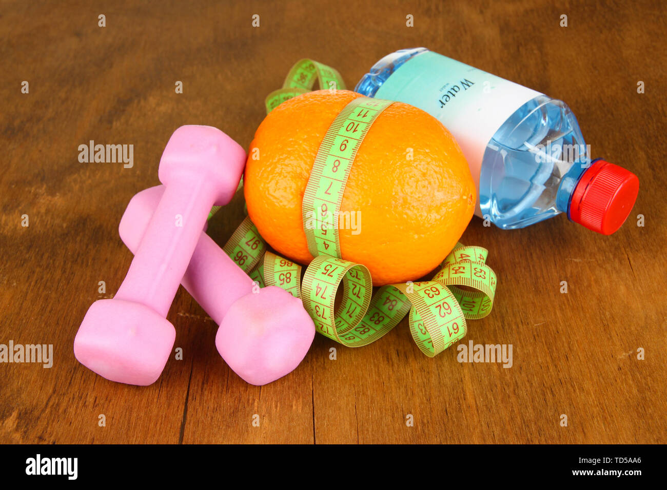Orange with measuring tape,dumbbells and bottle of water, on wooden background - Stock Image