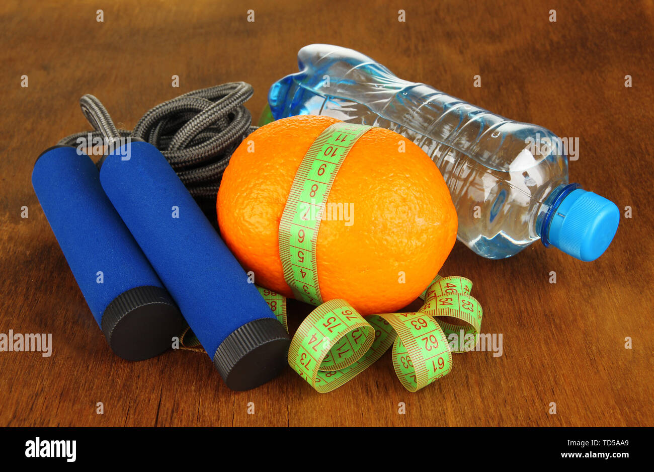 Orange with measuring tape,skipping rope and bottle of water, on wooden background - Stock Image