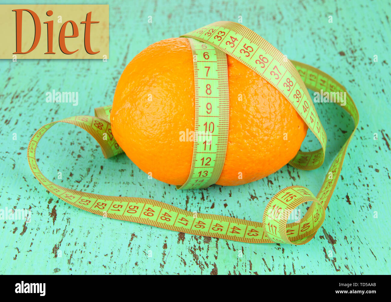 Orange with measuring tape, on color wooden background - Stock Image