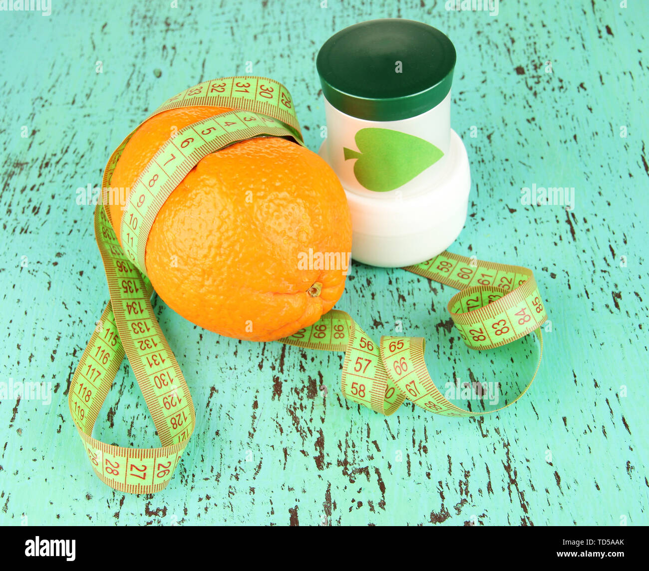 Orange with measuring tape and body cream, on color  wooden background - Stock Image