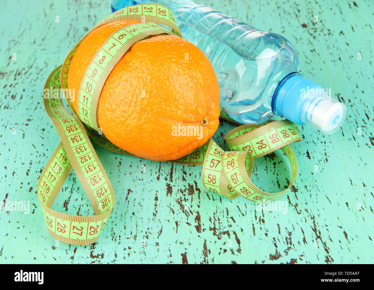 Orange with measuring tape, bottle of water, on  color wooden background - Stock Image