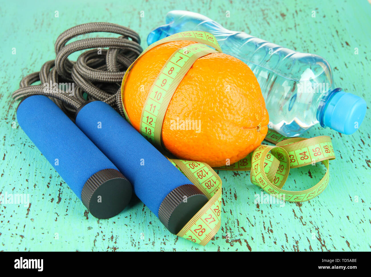Orange with measuring tape,skipping rope and bottle of water, on color wooden background - Stock Image