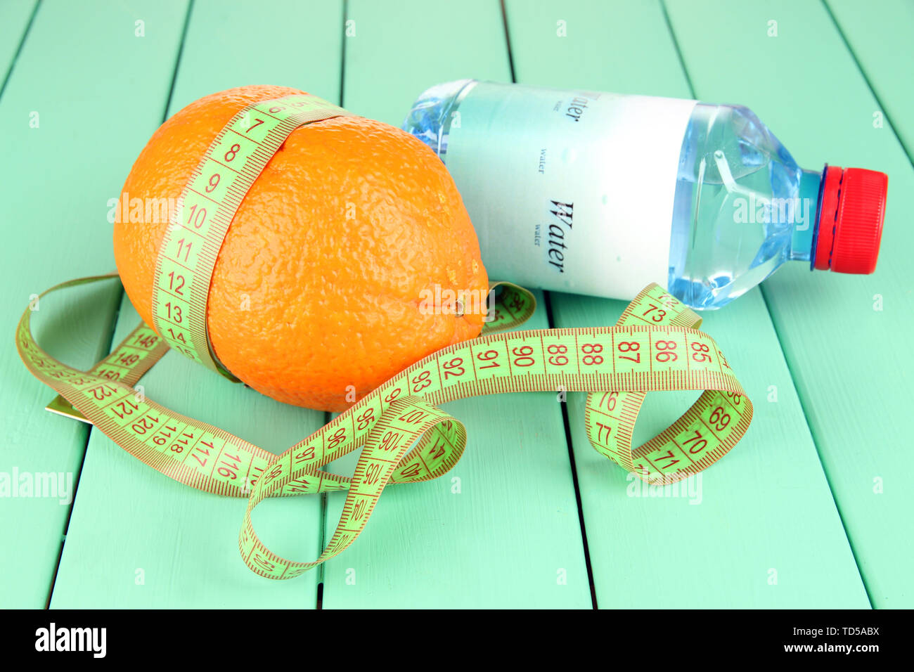 Orange with measuring tape, bottle of water, on wooden background - Stock Image