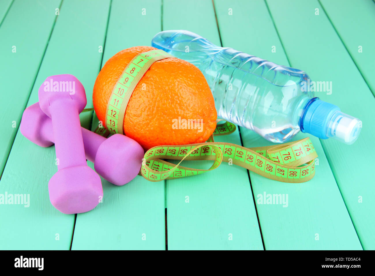 Orange with measuring tape, dumbbells and bottle of water, on color wooden background - Stock Image