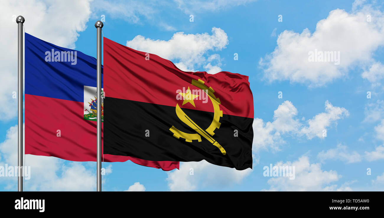 Haiti and Angola flag waving in the wind against white cloudy blue sky together. Diplomacy concept, international relations. - Stock Image
