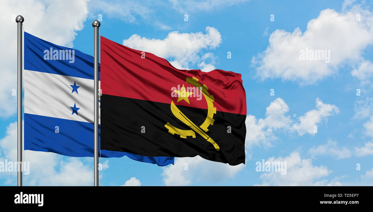 Honduras and Angola flag waving in the wind against white cloudy blue sky together. Diplomacy concept, international relations. Stock Photo