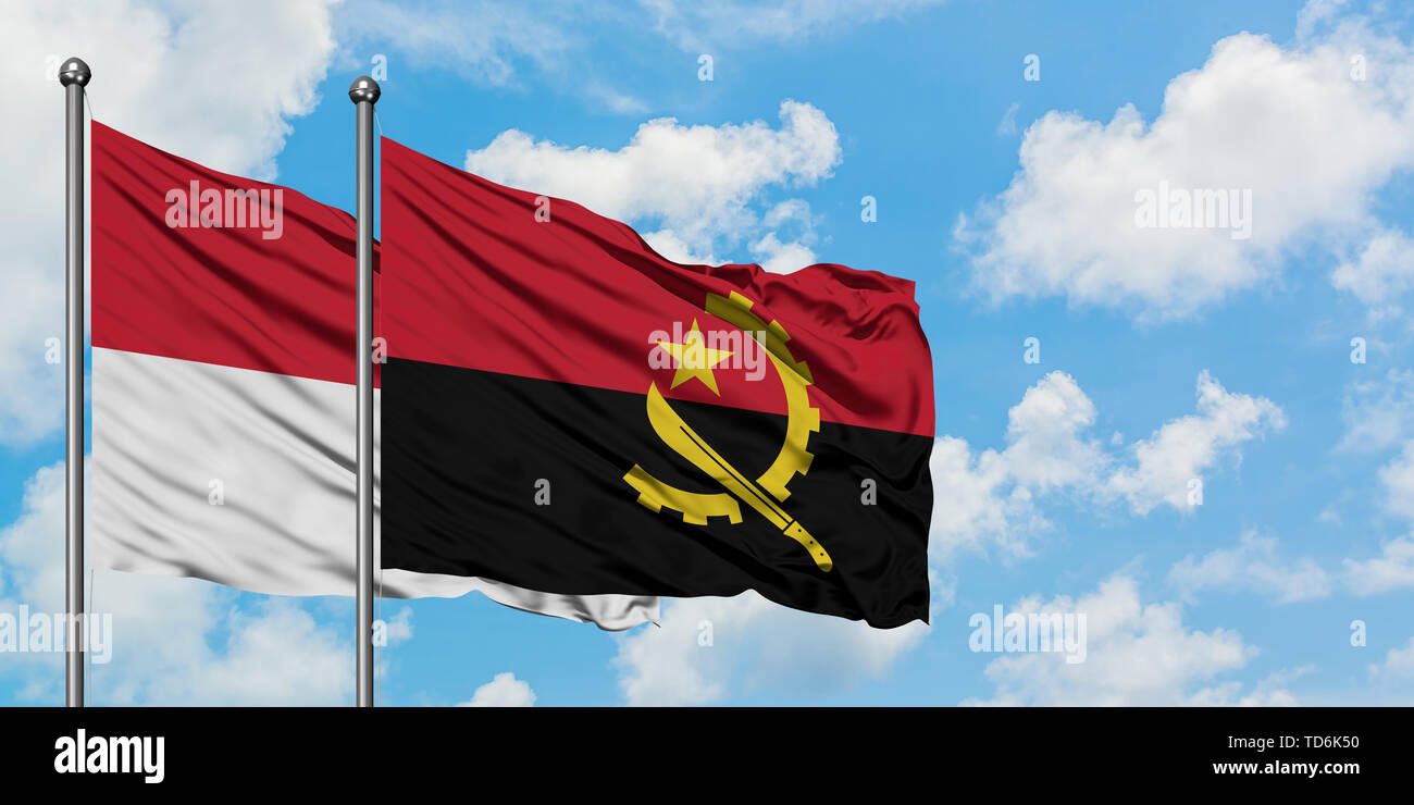 Iraq and Angola flag waving in the wind against white cloudy blue sky together. Diplomacy concept, international relations. - Stock Image
