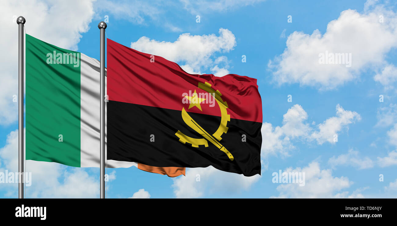 Ireland and Angola flag waving in the wind against white cloudy blue sky together. Diplomacy concept, international relations. - Stock Image