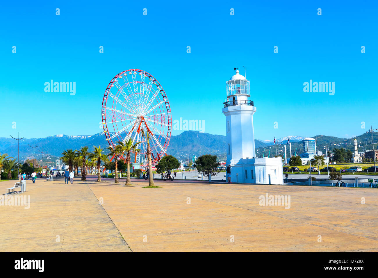 Batumi, Georgia - April 30, 2017: Ferris wheel, city panoramic landscape with palm trees and mountain peaks of Batumi, Georgia summer Black sea resort - Stock Image