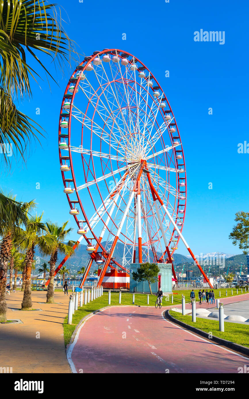 Batumi, Georgia - April 30, 2017: Ferris wheel, city panoramic landscape with mountain peaks, summer Black sea resort - Stock Image