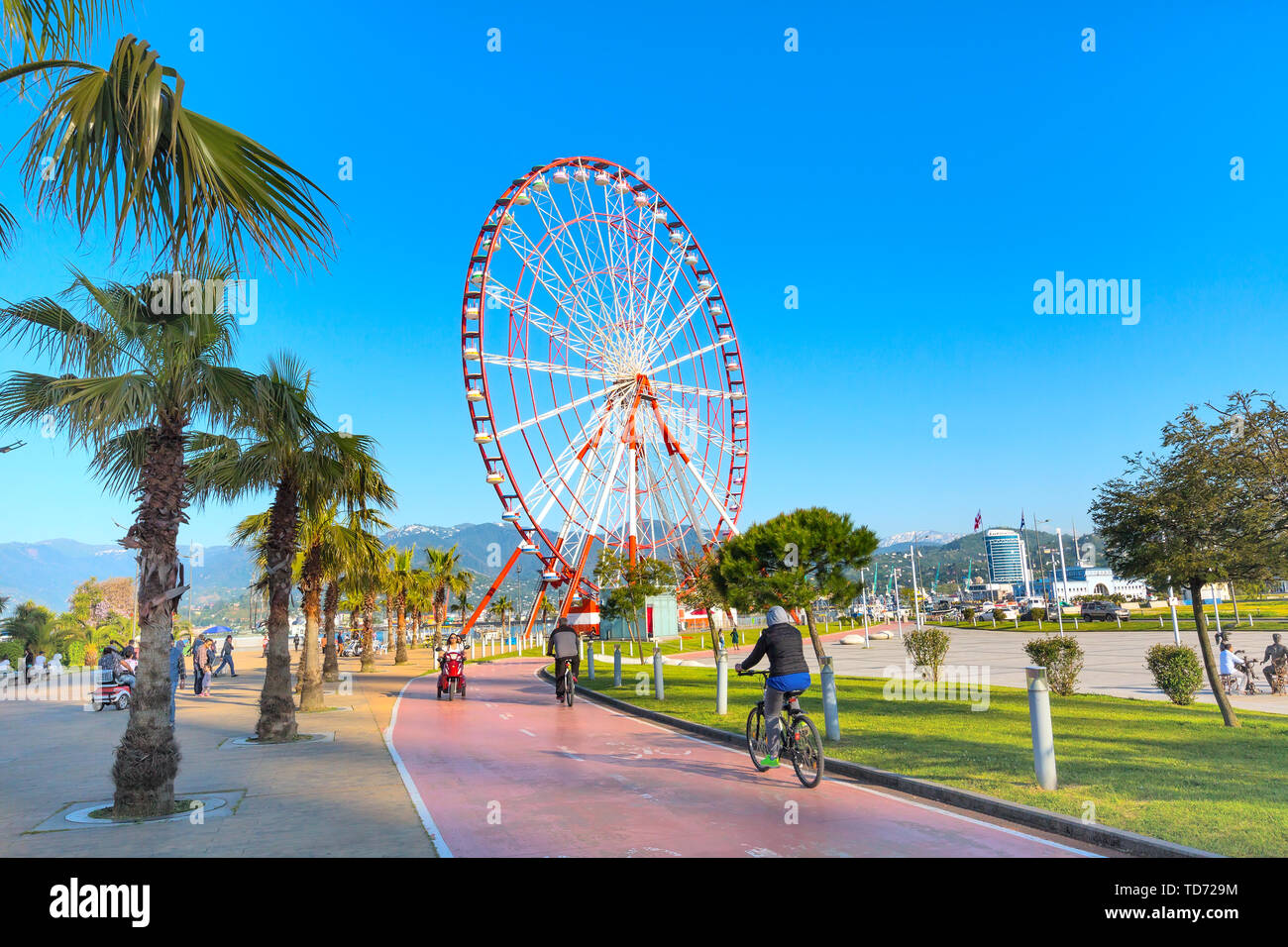 Batumi, Georgia - April 30, 2017: Ferris wheel, city panoramic landscape with port and mountain peaks of Batumi, summer Black sea resort - Stock Image