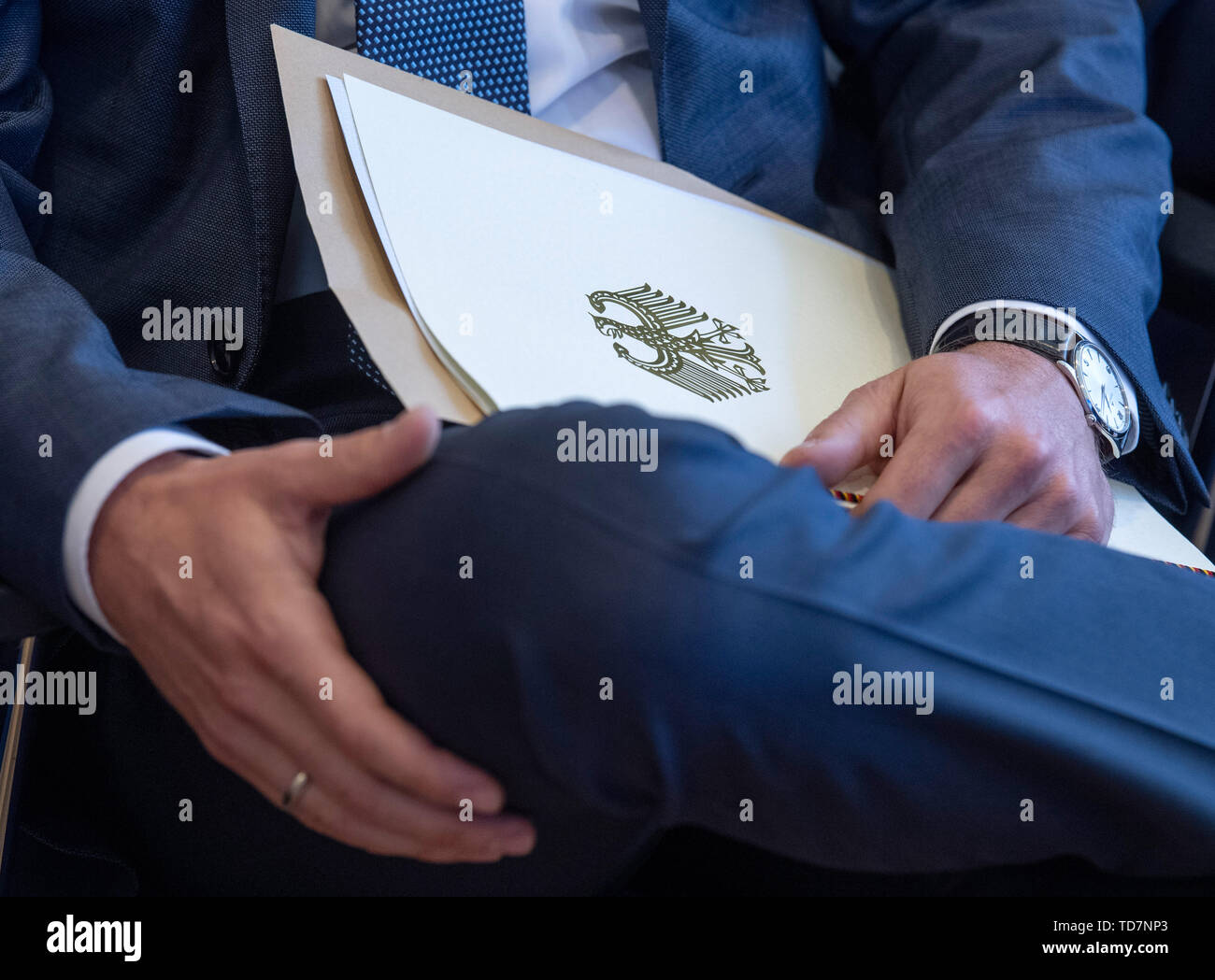 Mainz, Germany. 13th June, 2019. A golden federal eagle adorns the front of the 'certificate of acceptance' which the representative of a mobile phone company has just received. A total of four bidders took part in the auction, which generated total proceeds of 6.5 billion euros. Credit: Boris Roessler/dpa/Alamy Live News - Stock Image