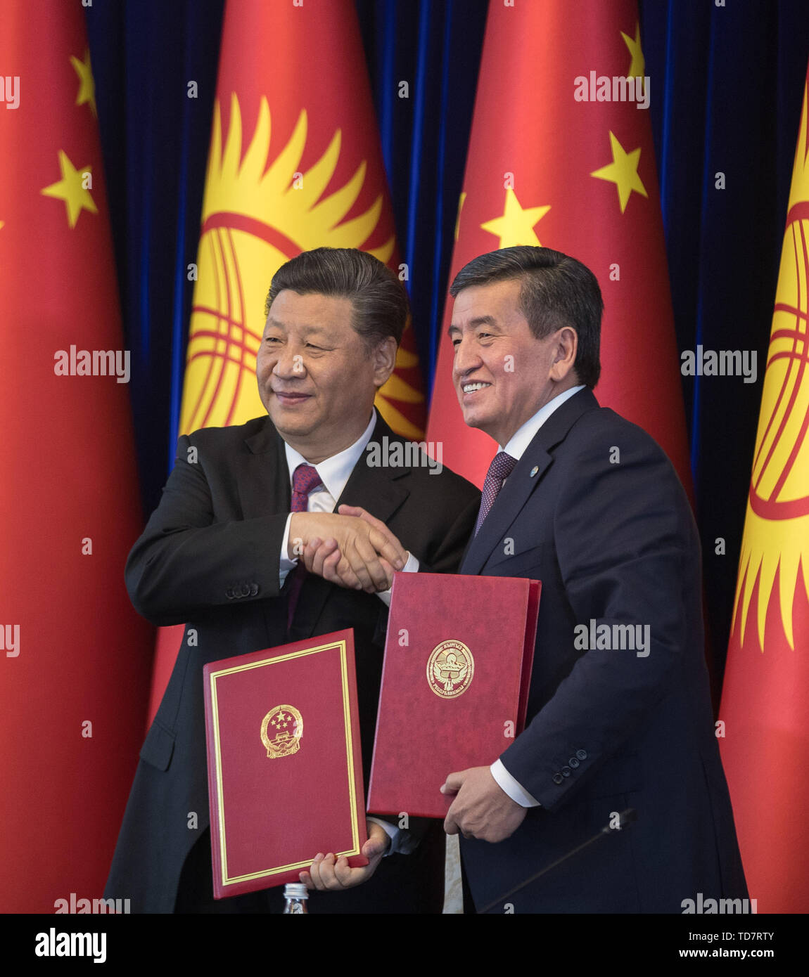 Bishkek, Kyrgyzstan. 13th June, 2019. Chinese President Xi Jinping shakes hands with his Kyrgyz counterpart Sooronbay Jeenbekov after signing the joint statement on taking their countries' comprehensive strategic partnership to new heights in Bishkek, Kyrgyzstan, June 13, 2019. Xi and Jeenbekov held talks here Thursday, agreeing to take their countries' comprehensive strategic partnership to new heights. Credit: Fei Maohua/Xinhua/Alamy Live News - Stock Image