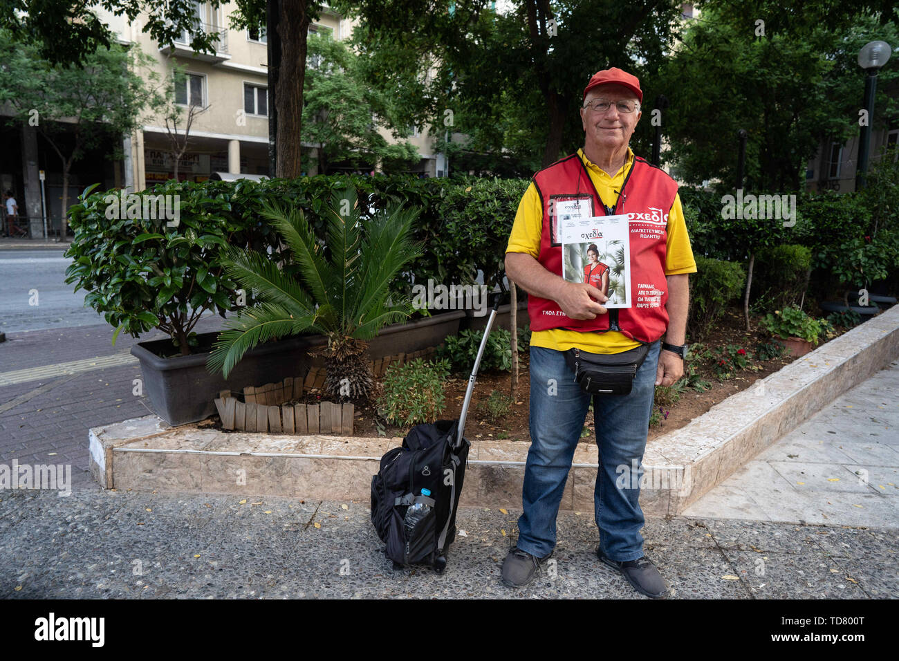 Athens, Athens, Greece. 12th June, 2019. Michael, 72, one of Shedia's street vendors, smiles at the camera with a copy of Shedia during the official tour.The tour of ''˜Invisible Athens' is organized by Shedia and goes into the parts of Athens that locals consider to be dangerous areas of the city and are generally avoided by tourists. Shedia is the only Greek street newspaper. The tour involves showing the conditions of homelessness in Athens. The Greek Ministry of Social Solidarity estimated that there were more than 1500 homeless people on the streets of Athens in 2018. (Credit Image: - Stock Image