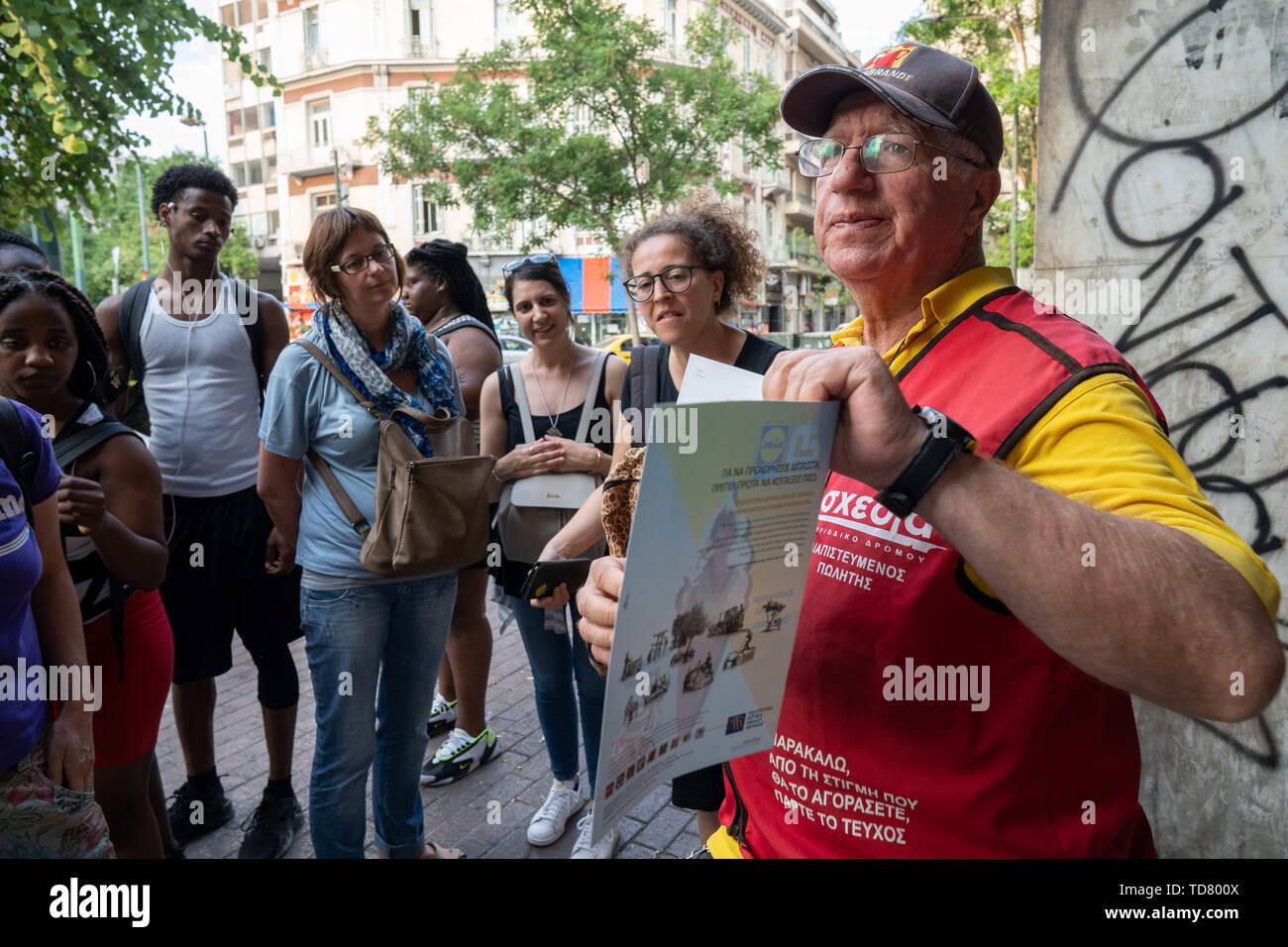 Athens, Athens, Greece. 12th June, 2019. Michael, 72, one of Shedia's street vendors, shows a copy of Shedia to participants of the Invisible Tour.The tour of ''˜Invisible Athens' is organized by Shedia and goes into the parts of Athens that locals consider to be dangerous areas of the city and are generally avoided by tourists. Shedia is the only Greek street newspaper. The tour involves showing the conditions of homelessness in Athens. The Greek Ministry of Social Solidarity estimated that there were more than 1500 homeless people on the streets of Athens in 2018. (Credit Image: © Lexie - Stock Image