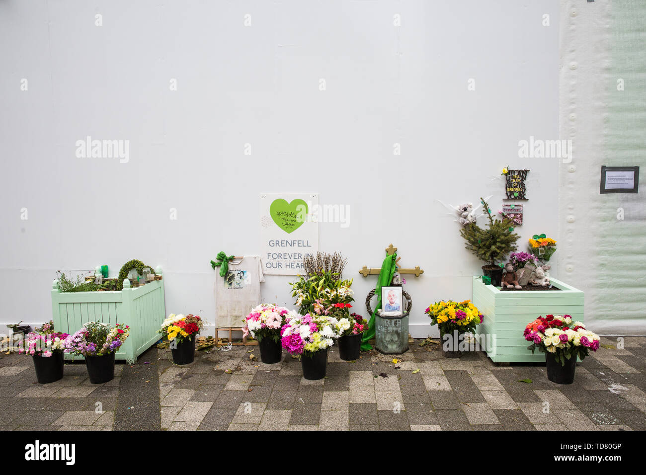 London, UK. 13 June, 2019. Tributes beneath the Grenfell Tower in North Kensington. Tomorrow, the Grenfell community will mark the second anniversary of the Grenfell Tower fire on 14th June 2017 in which at least 72 people died and over 70 were injured. Two years on, some family members remain in temporary accommodation and many are still traumatised. Phase 2 of the Grenfell Inquiry will begin in 2020, with criminal investigation findings expected to be sent to the Crown Prosecution Service in 2021. Credit: Mark Kerrison/Alamy Live News - Stock Image