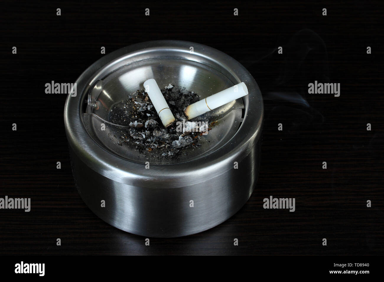Metal  ashtray with cigarette, isolated on black - Stock Image