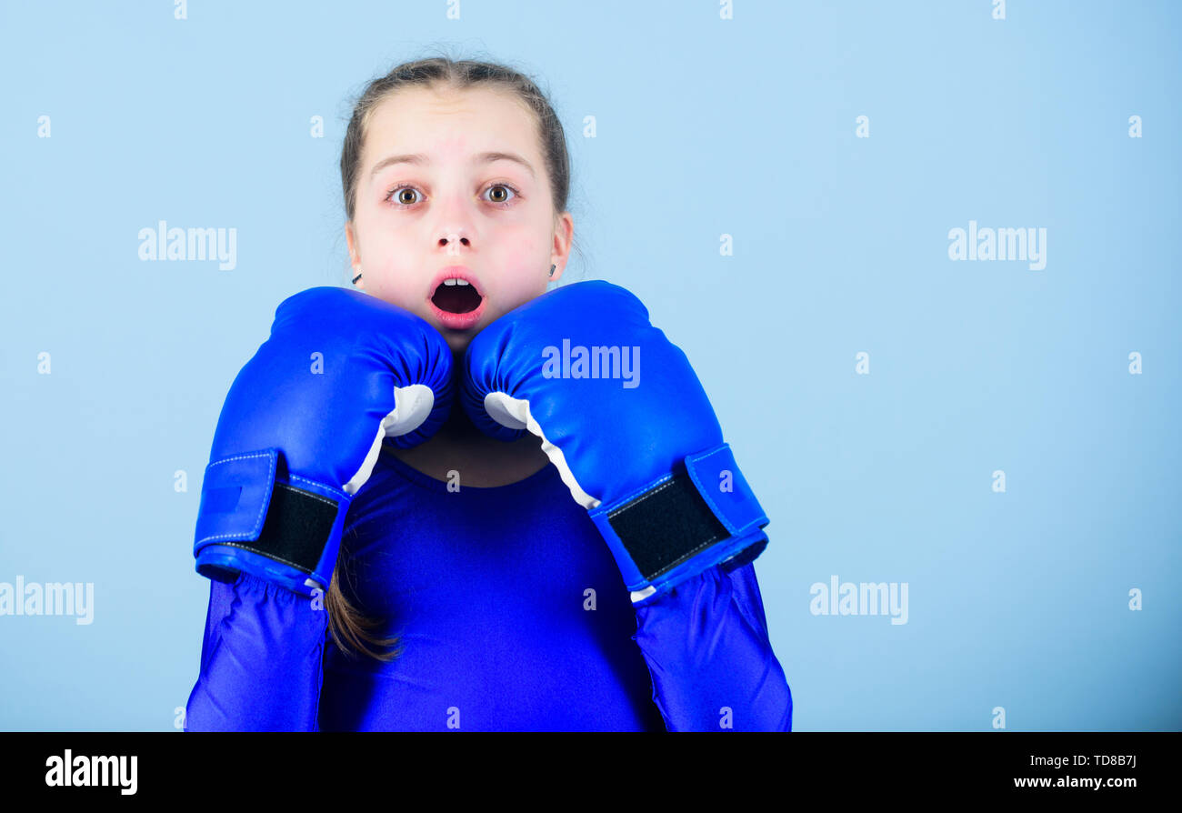Girl cute boxer on blue background. With great power comes great responsibility. Boxer child in boxing gloves. Female boxer change attitudes within sport. Risk of injury. Rise of women boxers. - Stock Image