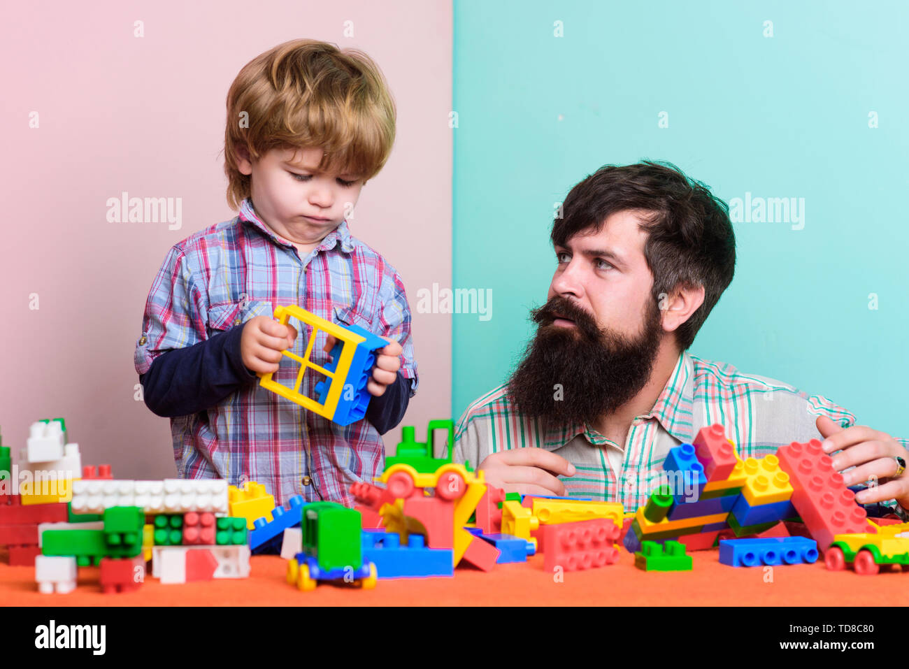 Bearded father and boy play together. Dad and kid build of plastic blocks. Useful toy. Child care development and upbringing. Father son game. Father  - Stock Image